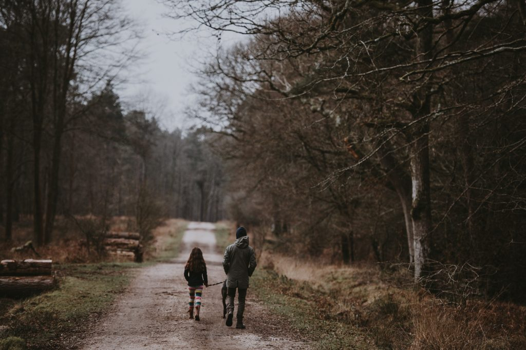 man, girl, dog walking in forest